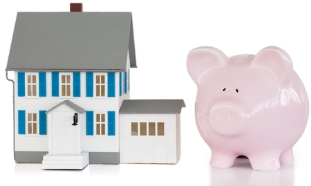 House and piggy bank against a white background  photo