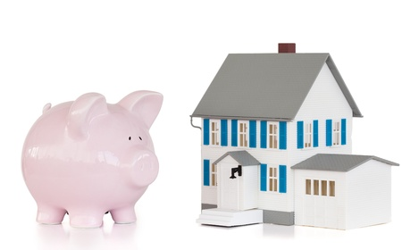 piggybank: House and pink piggy bank against a white background