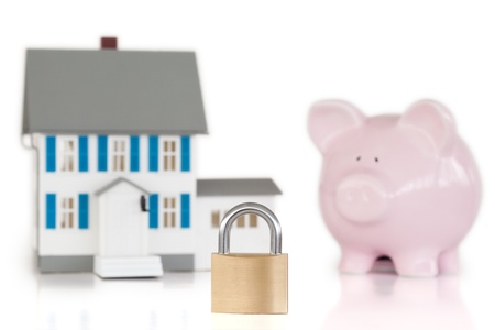 House locked with padlock and piggy bank against a white background  photo