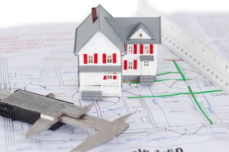 Close-up of toy house model and ruler on a plan against a white background Stock Photo - 10198860