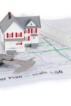 Close-up of toy house model and caliper on a plan against a white background photo