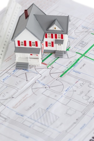 Close-up of toy house model and ruler on a plan against a white background photo