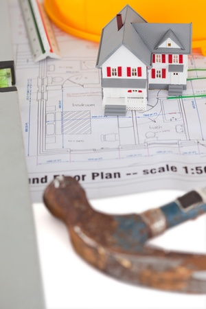 Toy house model with hammer and helmet on a plan against a white background photo
