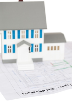 Toy house model on a ground floor plan against a white background photo