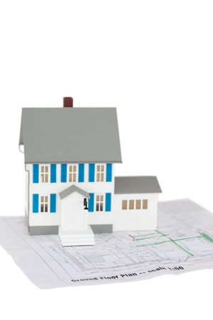 Grey toy house model on a ground floor plan against a white background photo