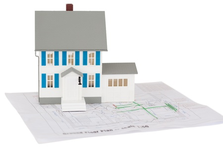 Closeup of a toy house model on a ground floor plan against a white background photo