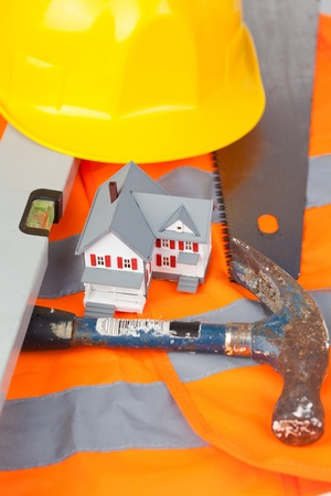Tools and miniature house on an orange jacket photo