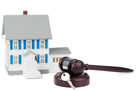 Grey toy house model with a key and a brown gavel against a white background photo