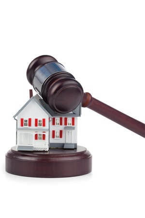 Closeup of a toy house model and a brown gavel against a white background photo