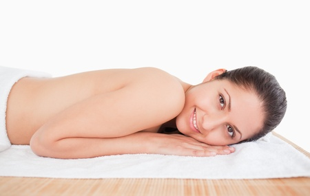 dark-haired young woman on a massage table white background photo