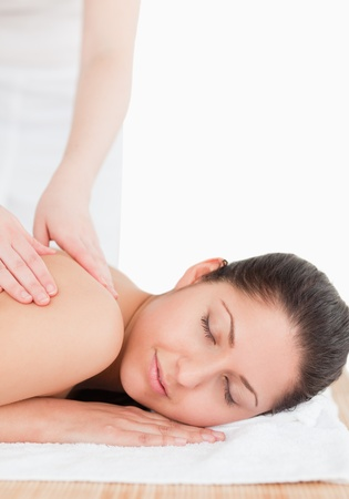 spa resort: young woman with her eyes closed having a massage in a spa Stock Photo