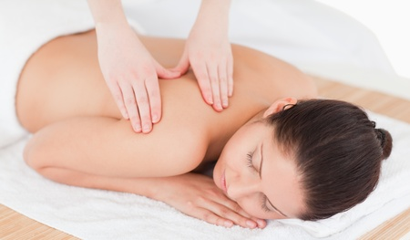 young woman having a back massage in a spa photo