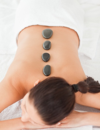 black stones massage on a dark-haired woman against white background photo