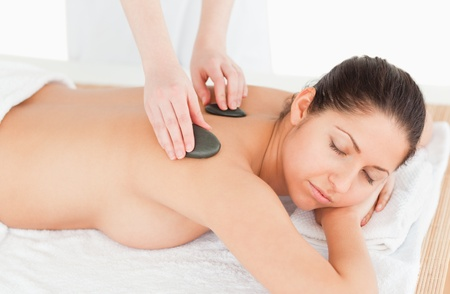 dark-haired woman relaxing while having a stone massage in a spa photo