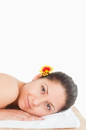 brunette with flower on her ear against white background photo