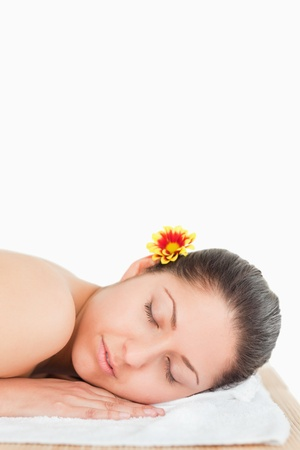 Eyes closed brunette with a flower on her ear Stock Photo - 10194628
