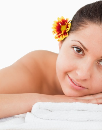 brown-haired woman with a flower on her ear in a spa photo