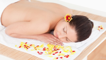 young woman sleeping with flower petals around her and a flower on her ear photo