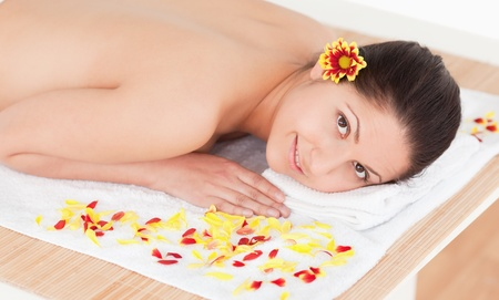 dark-haired woman lying on her belly with a flower on her ear surrounded by flowers photo