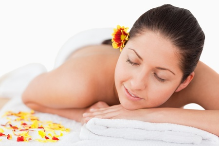 dark-haired woman closing her eyes and a flower on her ear lying on her belly photo