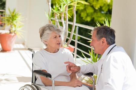 paraplegic: Senior arts praten met zijn patiënt Stockfoto