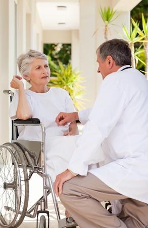 paraplegia: Senior doctor talking with his patient