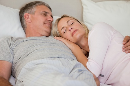 Beautiful couple sleeping on their bed photo