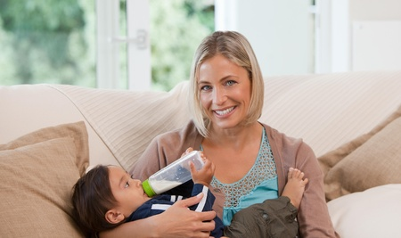 Mother giving a  bottle of milk to her son Stock Photo - 10193175