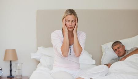 Woman having a headache while her husband is sleeping photo
