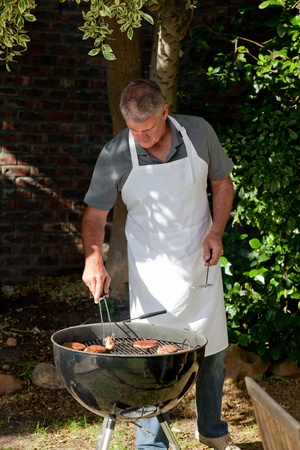 Handsome man having a barbecue in the garden Stock Photo - 10198614