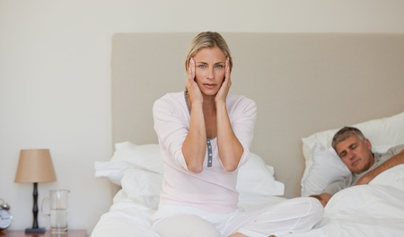 Woman having a headache while her husband is sleeping Stock Photo - 10193119