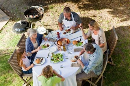 Adorable family eating in the garden photo