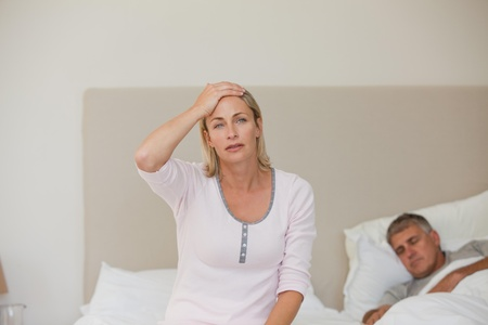 Woman having a headache while her husband is sleeping Stock Photo - 10192541