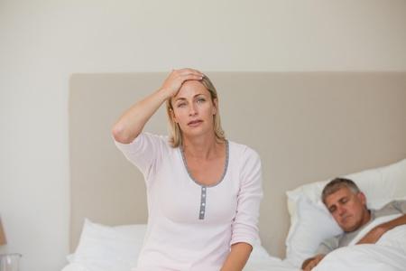 Woman having a headache while her husband is sleeping Stock Photo - 10192541