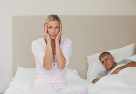 Woman having a headache while her husband is sleeping Stock Photo - 10192534