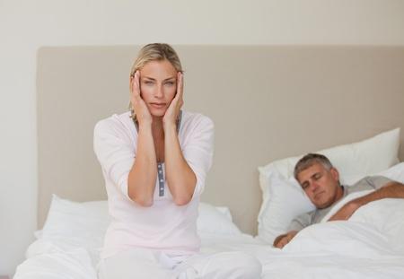 Woman having a headache while her husband is sleeping Stock Photo - 10192534