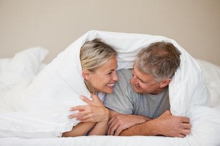 femme romantique: Couple couch� dans leur lit � la maison