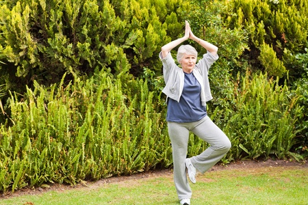 Mature woman doing her streches in the garden photo