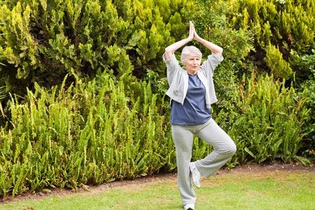 Starší žena dělá ji streches v zahradě Reklamní fotografie - 10207032