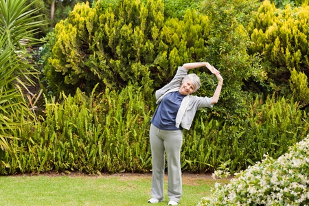 Retired  woman doing her streches in the garden photo