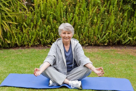 Retired woman practicing yoga in the garden photo