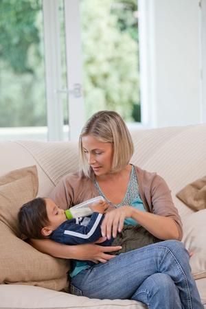 Madre dando un biberón de leche a su hijo Foto de archivo - 10198069