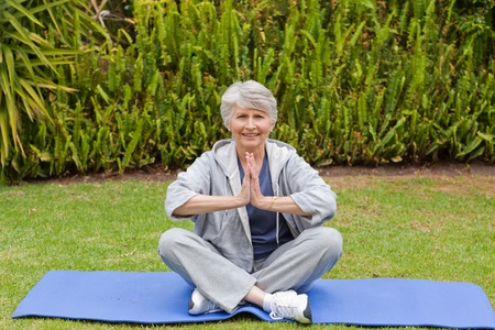 Retired woman practicing yoga in the garden Stock Photo - 10206455