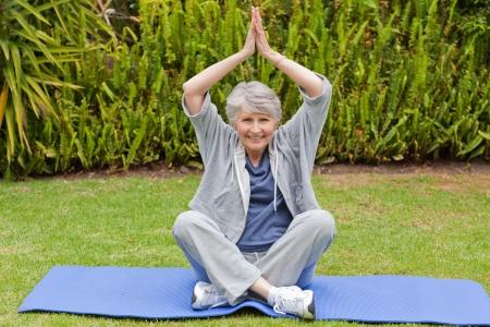 Senior Woman doing ihr erstreckt sich im Garten Lizenzfreie Bilder