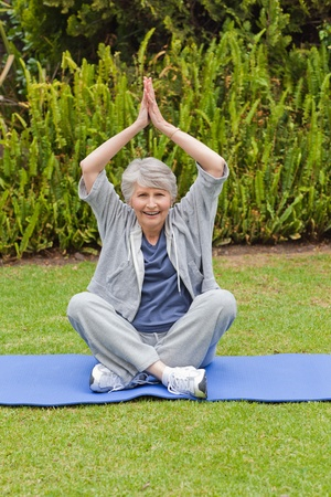Senior woman doing her streches in the garden photo