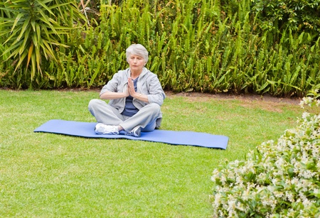 Senior woman doing her streches in the garden Stock Photo - 10206438