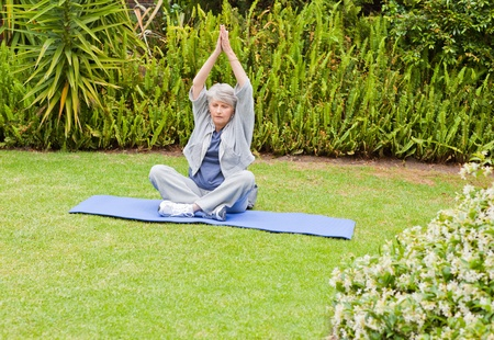 Senior woman doing her streches in the garden photo