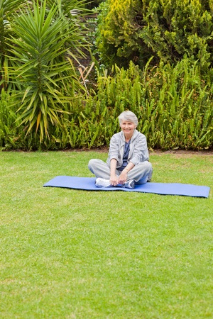 Senior woman doing her streches in the garden Stock Photo - 10206860