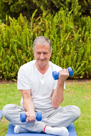 touching toes: Retired man doing his exercises in the garden