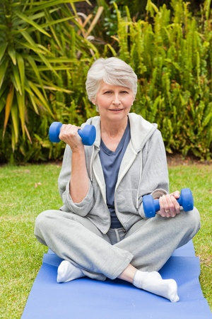 Retired woman doing her exercises in the garden Stock Photo - 10205988